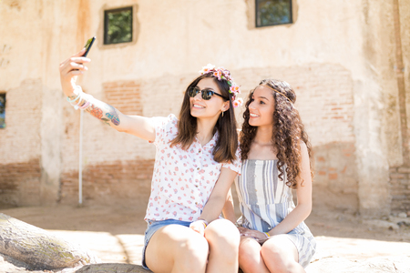 Beautiful smiling soul sisters taking selfie on smart phone while hanging out together in summer Фото со стока