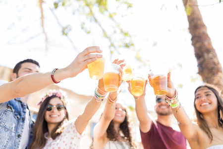 Best friends raising beer glasses while celebrating their friendship in summer party