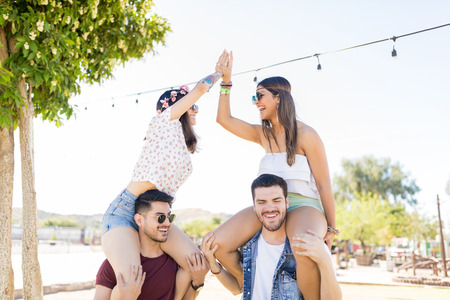 Carefree women giving high five while sitting on shoulders of boyfriends at party