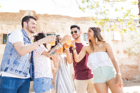 Cheerful young friends toasting beer glasses during summer party celebration