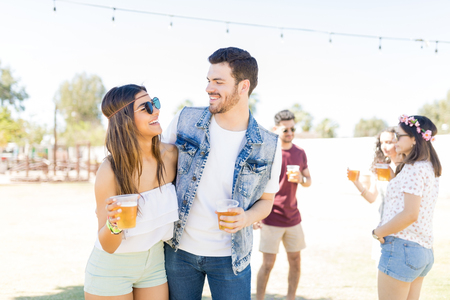 Beautiful young lovers looking at each other while enjoying beer at music festival
