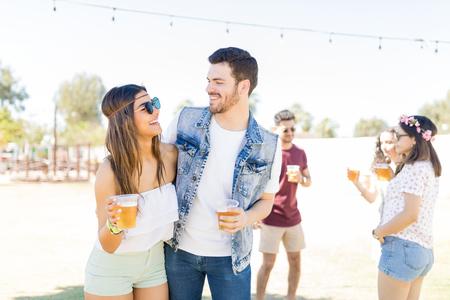 Piękni młodzi kochankowie patrzący na siebie przy piwie na festiwalu muzycznym
