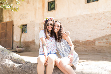 Happy loving best friends in casuals sitting together on log during sunny day