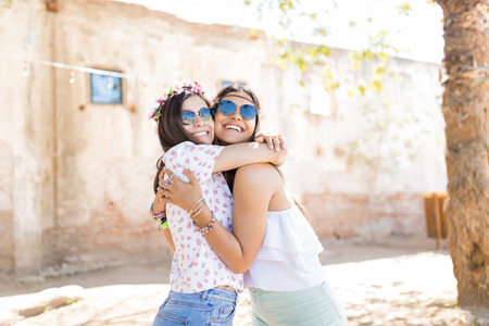 Affectionate and cheerful young women giving a tight hug to each other