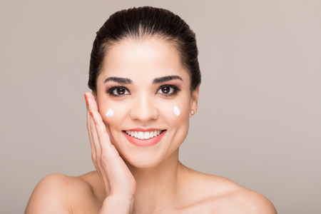 Smiling good looking Hispanic woman with bare shoulders and some facial cream on her face