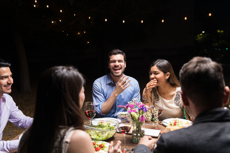 Cheerful friends having fun while enjoying food at party during night
