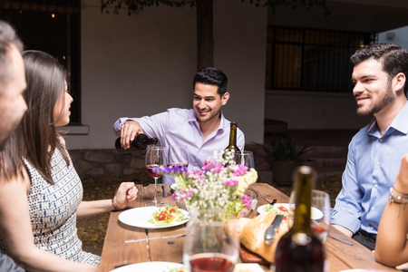 Good looking man pouring wine into glasses for friends while having dinner