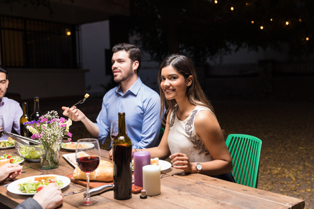 Portrait of attractive young woman smiling while having food with friends at night