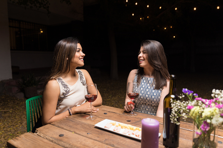 Hispanic female friends talking while enjoying wine at dinner party in night