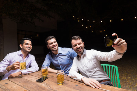 Man taking selfie with friends on smartphone while enjoying beer at party outside house Archivio Fotografico