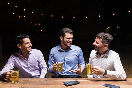 Happy friends talking over beer at dining table in dinner party Archivio Fotografico