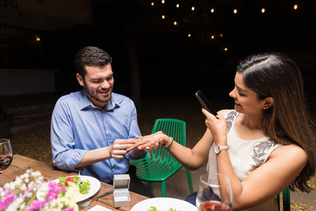 Woman photographing boyfriend putting ring on her finger at dining table in backyard party Imagens