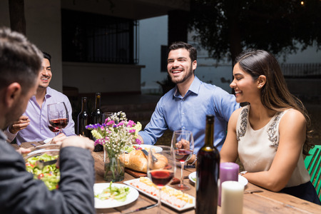 Handsome man spending leisure time with friends at dinner table