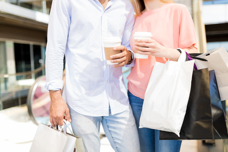 Midsection of young man and woman with disposable coffee cups and bags in shopping mall