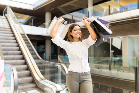 Portrait of charming woman with bags enjoying weekend shopping in mall