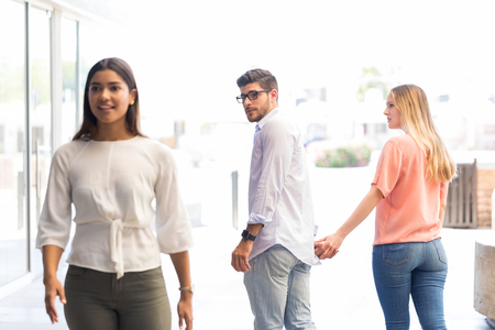 Jeune homme vérifiant une autre femme en marchant avec sa petite amie dans un centre commercial