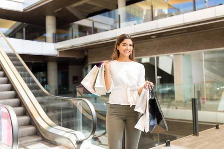 Smiling Hispanic woman carrying shopping bags while making eye contact