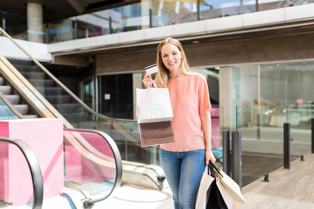 Portrait of pretty young woman shopping with credit card in mall