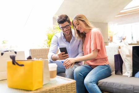 Feliz pareja mirando fotografías hizo clic en el teléfono inteligente en el centro comercial