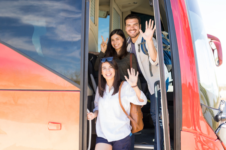 Portrait of happy friends gesturing at the entrance of tour bus