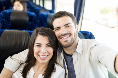 Affectionate smiling lovers taking selfie in travel bus