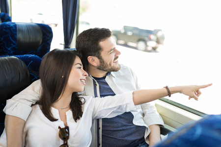 Woman pointing while man looking through window in travel bus