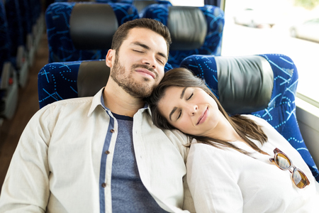 High angle view of couple napping together while traveling in bus Imagens