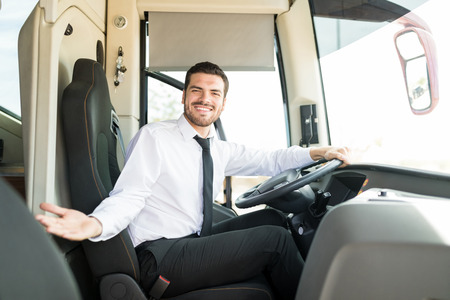 Portrait of happy driver inviting on board of intercity bus