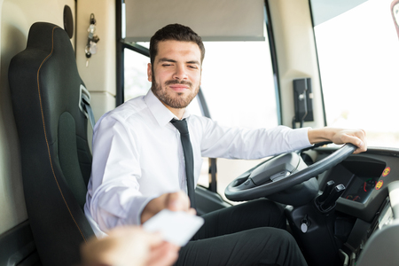 Confident young bus driver wearing uniform while selling tickets Фото со стока