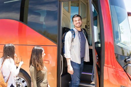 Smiling male tourist with female friends boarding tour bus