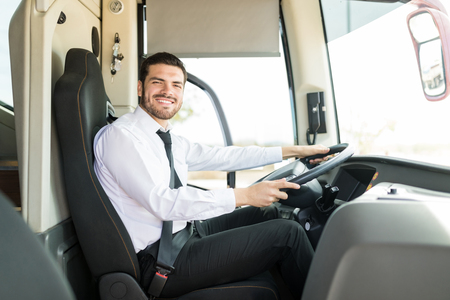 Portrait of attractive professional driver with confident look driving tourist bus