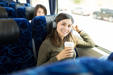 Happy young passenger having coffee while enjoying music in bus journey