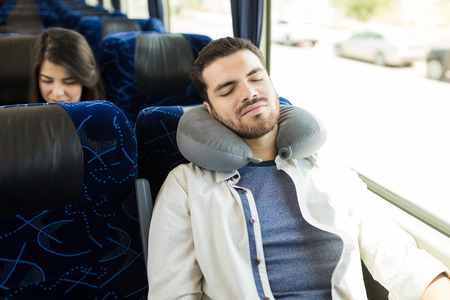 Hispanic man with neck pillow napping during bus journey