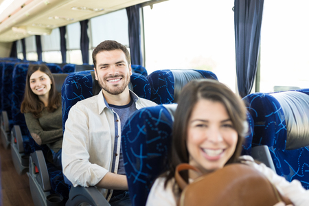 Happy Hispanic man with female friends traveling in bus
