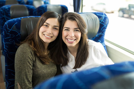 Jolies femmes brunes profitant d'une visite de la ville en bus de luxe