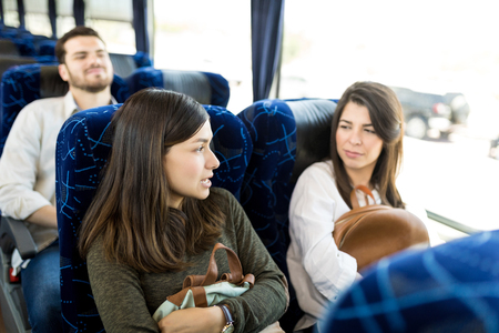 Latin female friends talking while sitting in travel bus