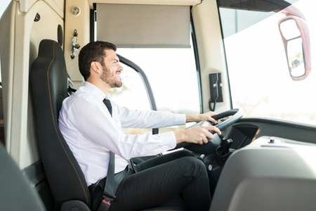 Side view of good looking man sitting on bus drivers seat and smiling