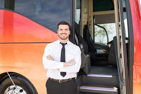 Portrait of good looking driver standing arms crossed outside intercity bus Фото со стока