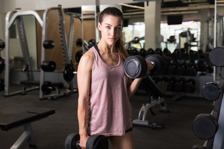 Determined young woman exercising with weights in health club