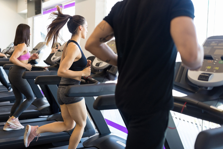 Male and female friends doing workout on treadmill in modern gym