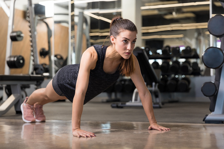 Full length of fit woman doing press-ups for perfect body in fitness club