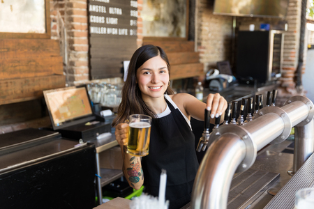 Smiling young Hispanic bartender serving beer in glass at bar