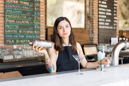 Confident Latin barmaid mixing alcoholic drink at bar counter in restaurant