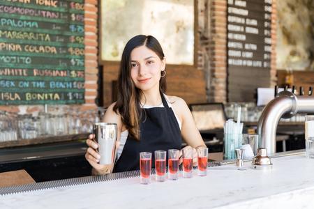 Confident Latin bartender preparing drinks at bar counter