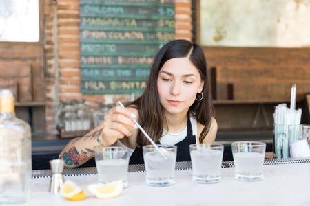 Hispanic barmaid mixing cocktail in glasses on countertop at bar 版權商用圖片