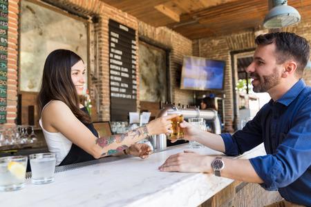Smiling Hispanic barmaid serving beer to male customer at bar