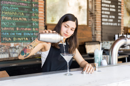 Professional female bartender pouring cocktail into glass at bar counter