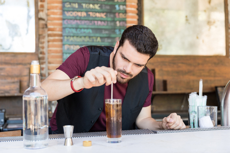 Barman stirring tasty alcoholic cocktail in glass on the bar counter at restaurant Stock Photo