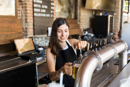 Smiling barmaid pouring beer from tap in glass at bar