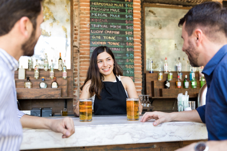 Smiling bartender serving alcoholic beverages to customers at restaurant